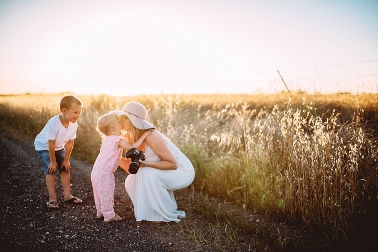 Mom photographer getting kissed by toddler while holding camera