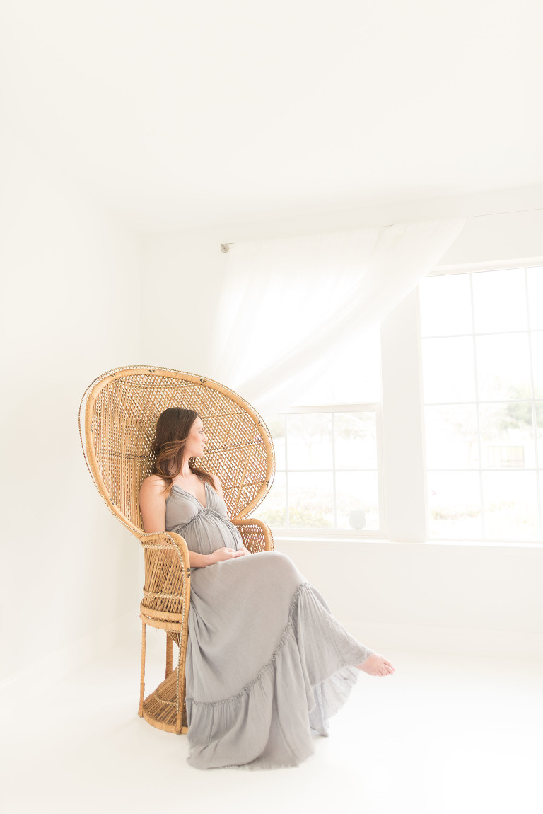 A pregnant woman sits in a large chair while her Sacramento Maternity photographer captures the moment.