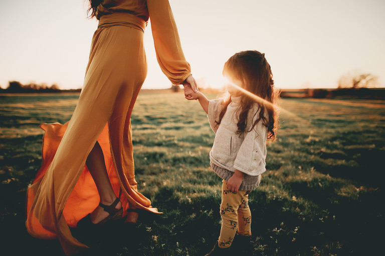 A little girl holds her mama's hand.