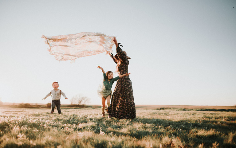 A mother holds a flying blanket, captured by the best family photographer in Sacramento.