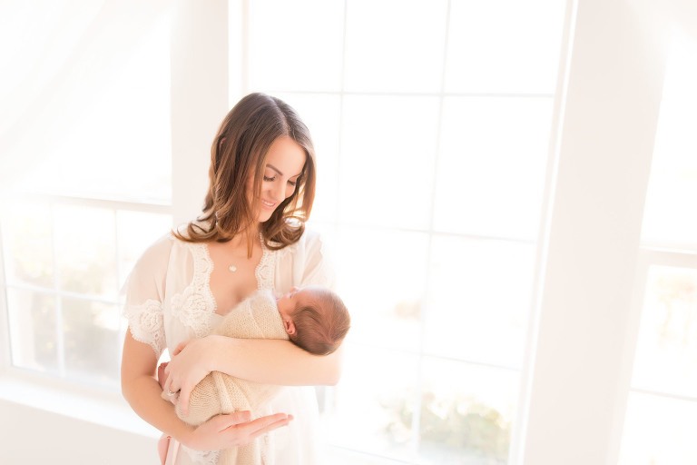 A mother holds her newborn | Sacramento Newborn And Family Photographer