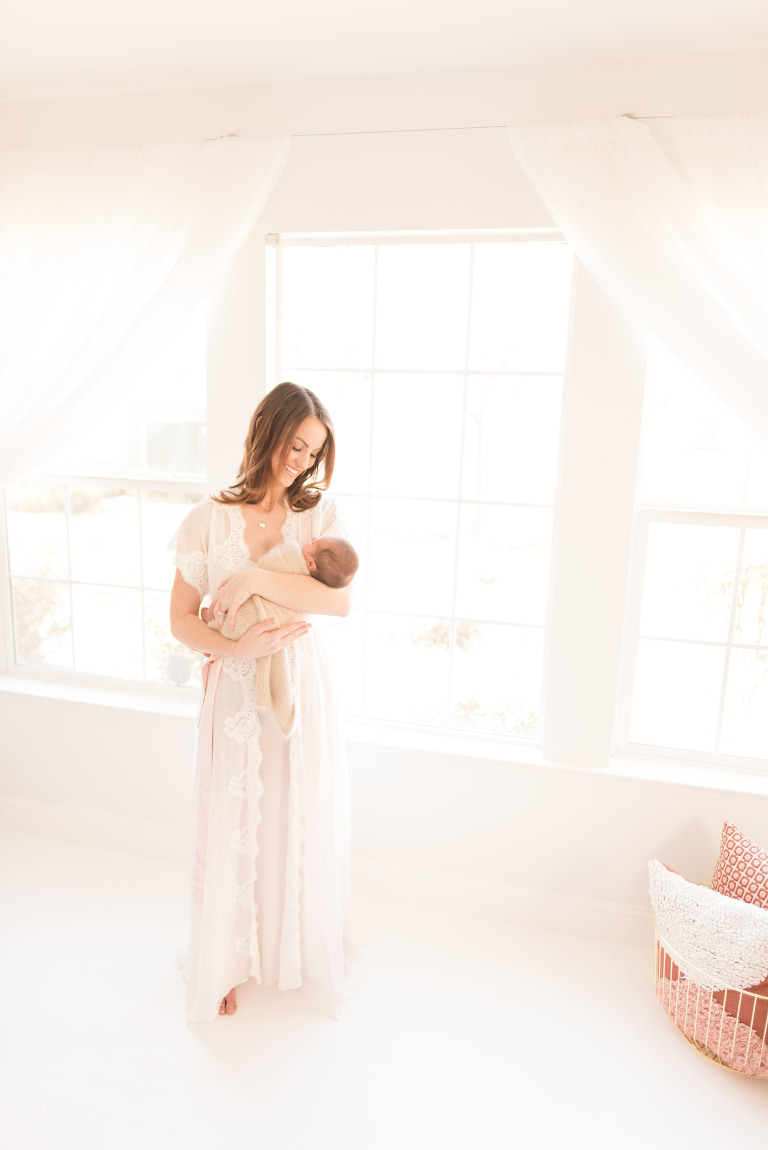 A new mother stands by a window with her baby | Sacramento Newborn And Family Photographer