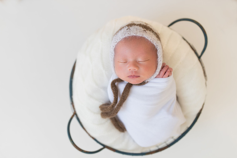 A baby is in a wire basket