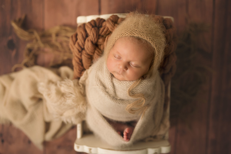 A newborn baby girl sleeps on top of a textured brown blanket.