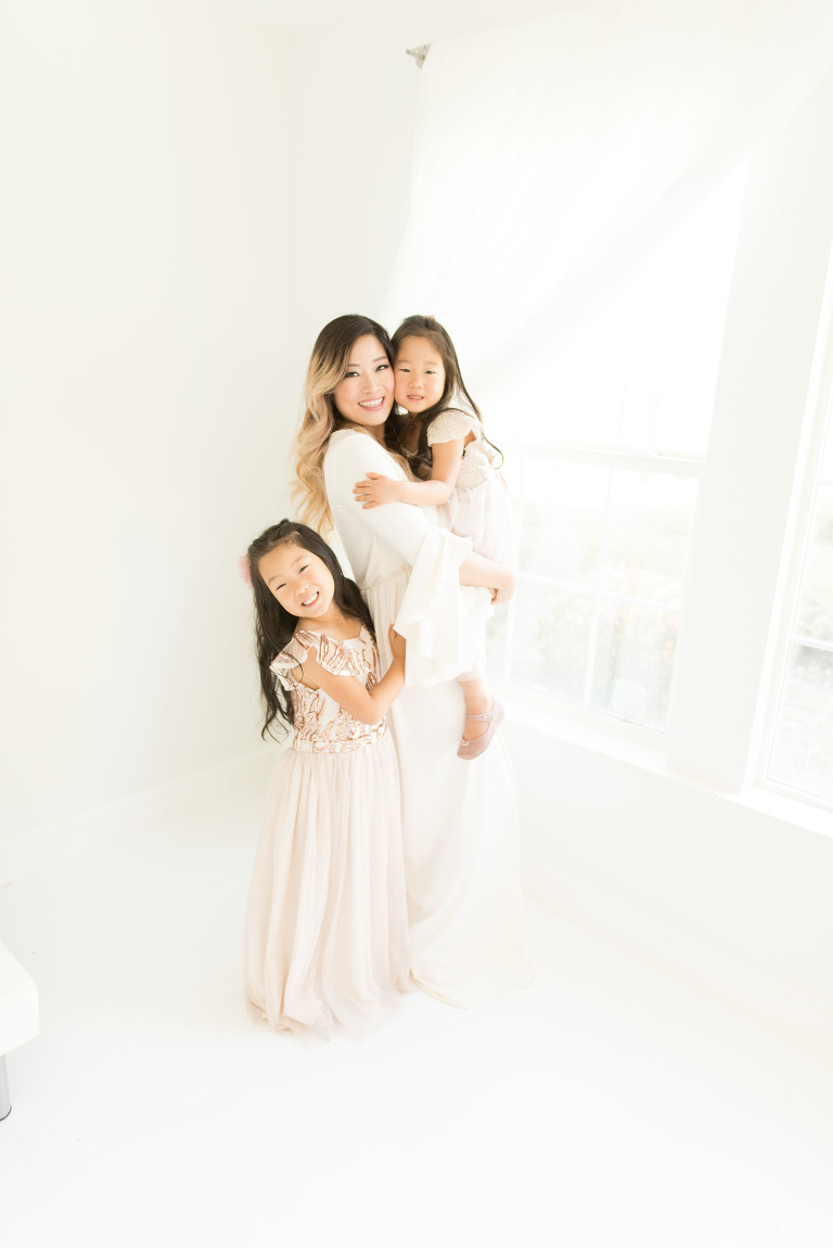 A pregnant mom holds younger daughter while older daughter hugs her leg in the studio captured by Sweet Beginnings Photography by Stephanie