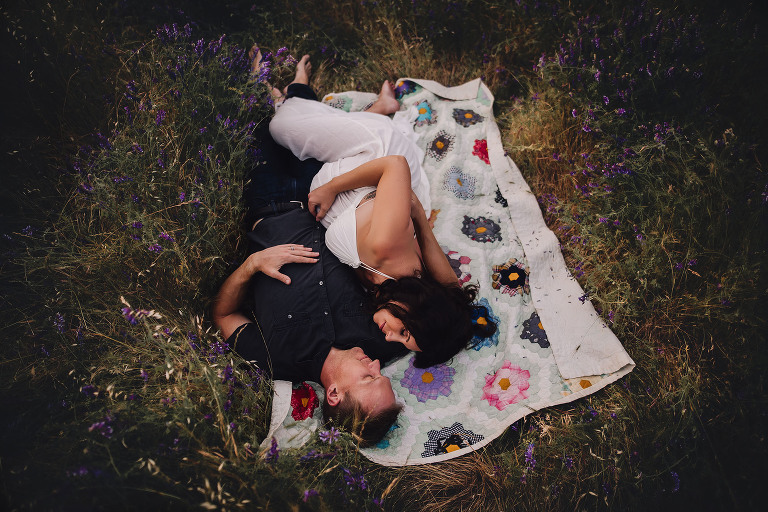 Husband and pregnant wife lay on a blanket in wildflowers captured by Sweet Beginnings Photography by Stephanie