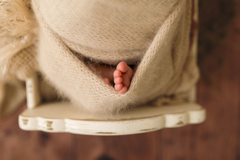 A newborn's foot peeks out of a blanket.