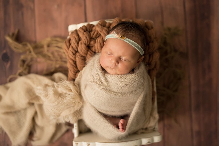 A baby sleeps during her newborn session with a Sacramento area baby photographer.
