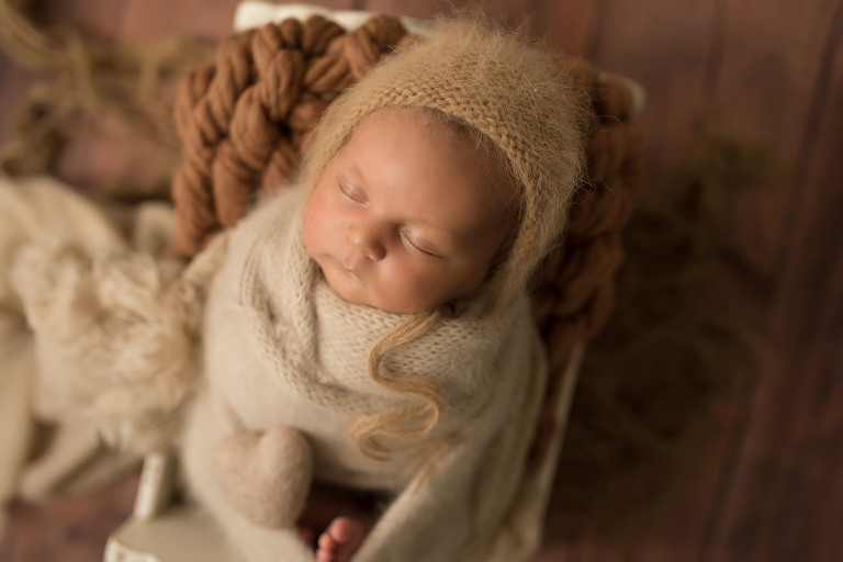 A newborn naps peacefully while wrapped in a soft blanket.