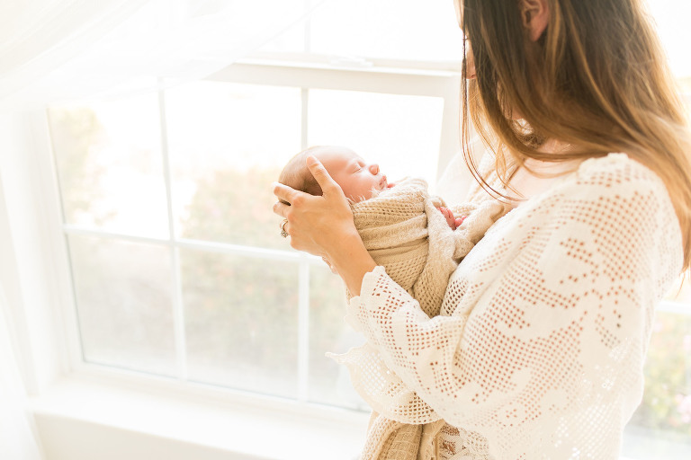 Mother gently strokes baby's head standing by the window captured by Sweet Beginnings Photography by Stephanie