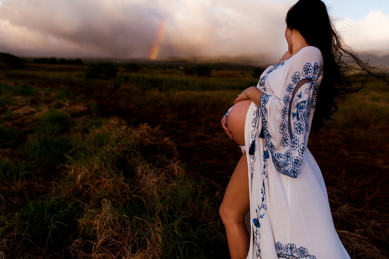 Pregnant mom holds her belly in Fillyboo dress looking at Maui rainbow captured by Sweet Beginnings Photography by Stephanie