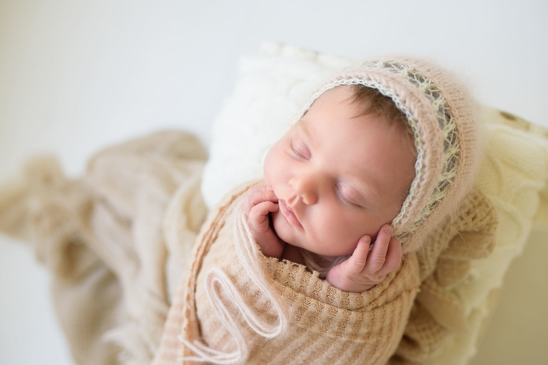 Newborn baby sleeping in the studio dressed in beige