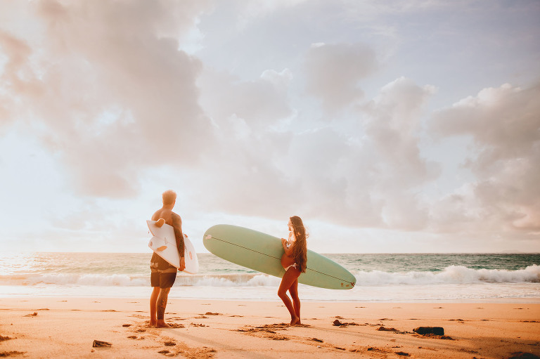 Pregnant couple on the beach with surfboards